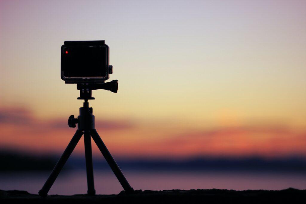 Muestra una cámara de acción sobre un tripié, accesorio indispensable en un equipo de vlogging